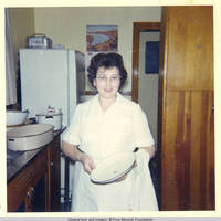 Mildred Hahlen standing in kitchen holding pot lid