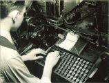 Student at typesetting machine in Close Hall, The University of Iowa, 1920s