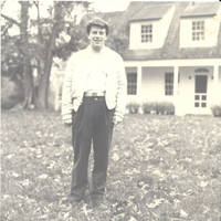 John, Jr. standing behind White house in the Fall