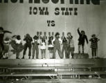 Students dressed in country costumes performing a country song on the night before Homecoming, 1969
