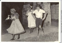 Carmen in uniform center dancing with two other women in Tobago