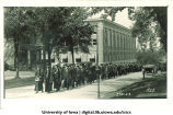 University President Walter Jessup and President Emeritus Thomas Macbride lead commencement procession walking east on Market Street past Trowbridge Hall on left, The University of Iowa, June 1922