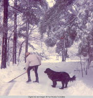 Ainsley Bernard shoveling snow with Sadie, the dog
