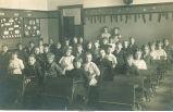 Grade 3 schoolchildren sitting at desks, Tama, Iowa, 1900s