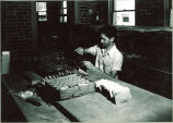 Geology student working with samples in a laboratory, The University of Iowa, 1930s