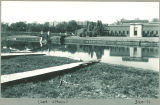 Wooden ramps to Iowa River with Art Building and Iowa Memorial Union pedestrian bridge, the University of Iowa, 1950s?