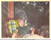 John, Jr. sitting in the smoke on the screened in porch