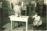 School girls painting table in junior primary classroom, The University of Iowa elementary school, March 31, 1930