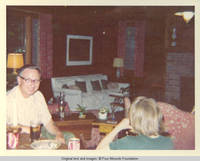Unknown man and John, Jr. seated at table drinking Coca Colas