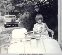 John, Jr. in golf cart with hand on driving bar, looking down