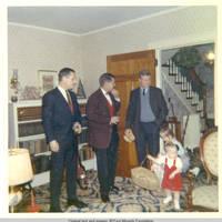 Bob, John, Sr., John, Nili and John, Jr. standing in living room during holidays