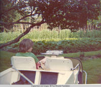 John, Jr. sitting in golf cart by vegatable garden