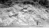 Man standing near oblique bedding at Sugar Creek lime quarries, Sugar Creek, Iowa, late 1890s or early 1900s