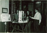 Engineering students dicusss a distillation factory model at Engineering Building open house, The University of Iowa, 1940s