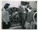 Professor Les Kelso instructing two cadettes about an airplane engine, 1943