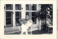 Man sitting in chair outside sun porch of White house