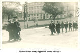 University of Iowa President Thomas Macbride, left, leading commencement procession west down Washington St., with MacLean Hall in background, The University of Iowa, 1910s