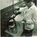 Student mixing compound in pharmacy laboratory, The University of Iowa, 1930s