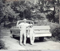 Bill and John, Jr. leaning on truck wearing matching plaid overhalls