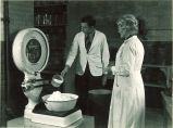 Professor observing student weighing pharmaceutical substance, The University of Iowa, 1930s