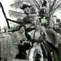 Homecoming attendant and two men with the Phi Delta Theta Victoryland homecoming lawn display, 1961