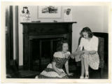 Betty Cue is seated showing a Curtiss P-40 Warhawk model plane to a cadette in the Memorial Union, 1943