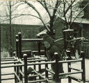 Small child climbing on a jungle gym in the snow, The University of Iowa, January 1938