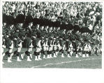 Line of Scottish Highlander bagpipers and dancers on athletic field, The University of Iowa, 1970s