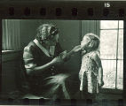 Woman holds a small girl's chin, The University of Iowa, May 10, 1941