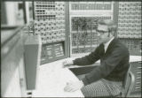 Researcher surrounded by control panels, 1973