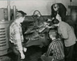 Professor showing three students the inner mechanics of a John Deere tractor, 1957