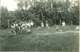 Students working in garden and feeding lamb during school open house, The University of Iowa, June 1, 1930