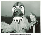 Herky and live hawk pose at football game, The University of Iowa, 1960s