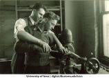 Instructor shows a student how to operate some equipment, The University of Iowa, 1920s