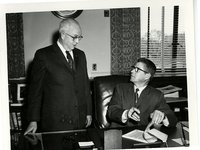 Men conversing over document
