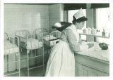 Nurse preparing to weigh baby in Children's Hospital, The University of Iowa, 1926