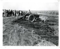 Group of Men Watch a Tractor Work the Land