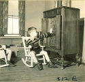 Boy touching a large wooden radio, The University of Iowa, January 12, 1938