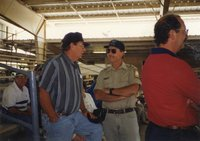 1997 - Dwight Stucker, award winner, Jeff Bergman, Commissioner and Bruce Trautman,  Area Conservationist from the Des Moines County Soil and Water Conservation District Office stand talking at the Ag Expo