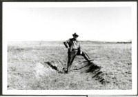 Harry Cadlin Displays a Damaged Area of a Farm Field