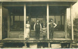 Men, woman and girl posing on porch of store, Morley, Iowa, 1910s