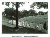 Commencement procession walking west on path near Quadrangle Residence Hall, The University of Iowa, June 1932
