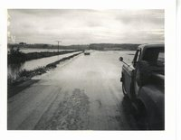 Water running across road in Tama Co., 1969