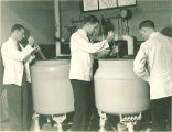 Students stirring compounds in large vats in pharmacy laboratory, The University of Iowa, 1930s