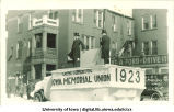 Officials with Iowa Memorial Union cornerstone on float in Mecca Day parade, The University of Iowa, 1923