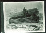 Man standing on wagon holding boiler equipment outside, The University of Iowa, 1890s