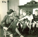 Small boy on piano bench helping a woman play violin, The University of Iowa, January 12, 1938