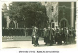Commencement procession filing past Old Dental Building, The University of Iowa, June 12, 1918