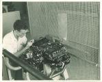 Engineering student working on engine in engineering laboratory, The University of Iowa, 1939