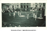 Women in costume dancing on the Pentacrest lawn near a maypole, The University of Iowa, June 1924